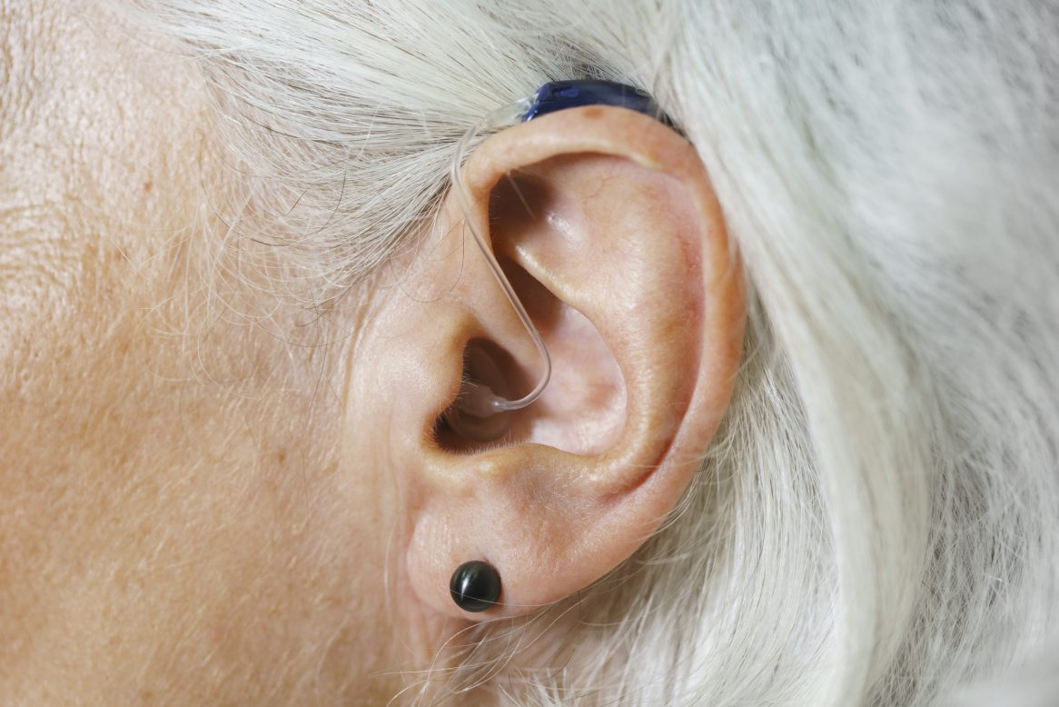 Close Up Of Woman With Gray Hair Wearing Hearing Aid