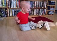 Baby ligt in een deuk om een schaaltje