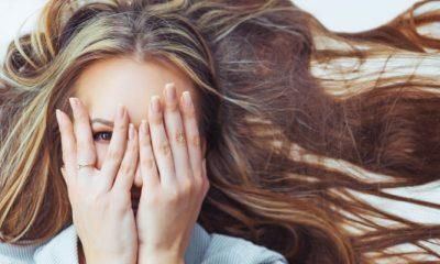 Vrouw ligt in bed met haar handen voor haar gezicht en denkt na over haar dromen