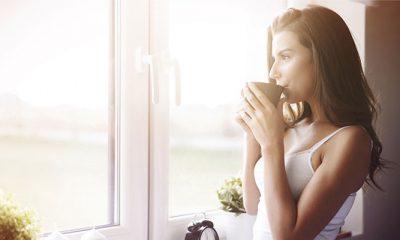Vrouw drinkt koffie bij raam, want ze drinkt geen alcohol in Dry January
