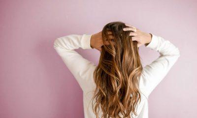 Vrouw heeft haar handen in haar haren. Ze heeft jeuk door hoofdluis.